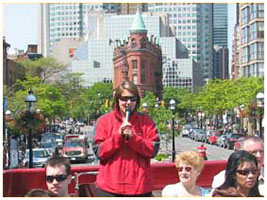 tour-guide-talking-about-Old-Town-Toronto-and-the-Market-with-the-Gooderham-Building-in-the-background